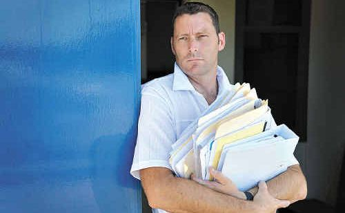 Storm Financial victim Sean McArdle with some of the huge pile of paperwork that piled up in the court case against the company.