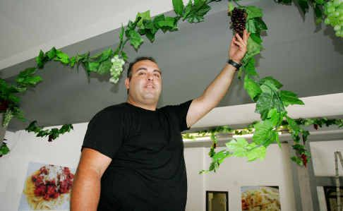 Rockhampton's newest restaurant owner Joseph Rizkallah decorates the inside of his new business, Di Carlos, on the corner of Bolsover and Fitzroy streets, ahead of today's opening.