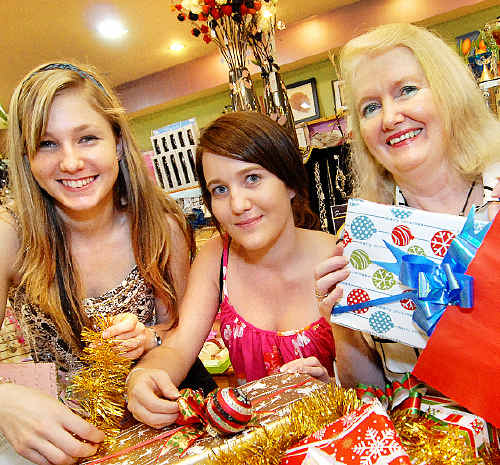 Samantha Gustafusson, left, Georgia Mason, 17, and Bodycare & Gifts Mt Pleasant owner Rita Smith get wrapped up in their Christmas shopping.