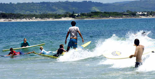 An experienced Byron Bay surfer weaves through the holiday crowds at The Pass in Byron Bay.