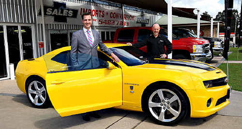 Dick Smith spokesperson Gray Bright (left) and Performax's Kevin Thoroughgood with the special edition Transformers Camaro that was won by a Brisbane man in the Dick Smith competition.