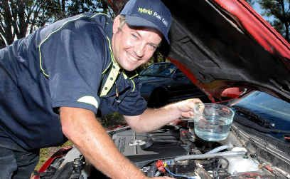 Glenn Old tops up with water at Mackay as he explains the virtues of his fuel cell device designed to use gas from water to improve fuel economy. Mr Old hopes to reduce public dependency on foreign oil