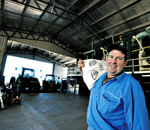 In the bag: Rain-fed biodynamic rice farmer Brett Slater pictured in front of the mill he has installed at his Fairy Hill property.