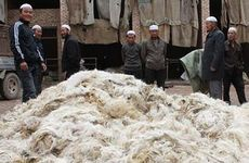 Hui men selling wool at a village market in China.