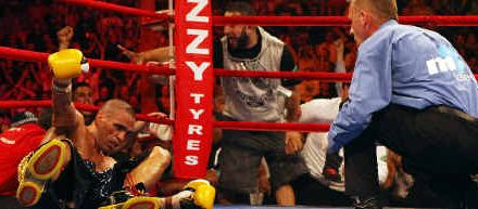 Garth Wood celebrates his knockout win over Anthony Mundine, pictured above on the canvas.