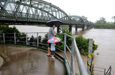 Andrew Rayer and his son Leonardo watch the Burnett River in flood.