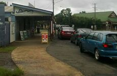 Cars line up for fuel out at the Southside Shop yesterday as floods move in.