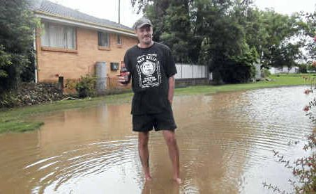 Grantham resident Graham Fry has a beer in a makeshift swimming pool formed at the back of the Grantham Hotel.