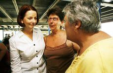 The Prime Minister Julia Gillard puts her arm around Sue Elliot as she and Beryl Harm recount their flood stories.