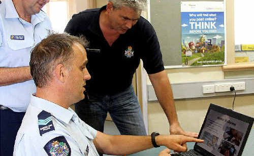Sergeant Nigel Dalton (seated) discusses internet safety with officer-in-charge of training Mackay District, Senior Sergeant Peter Grace and Senior Community Crime Prevention officer Ron Waters-Marsh.