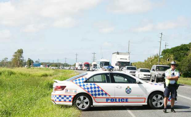 Traffic banked up on the Bruce Highway near Proserpine after a man died in a car crash on Friday at about 7.35am. Directing traffic is Whitsunday Police senior constable Simon Docking.