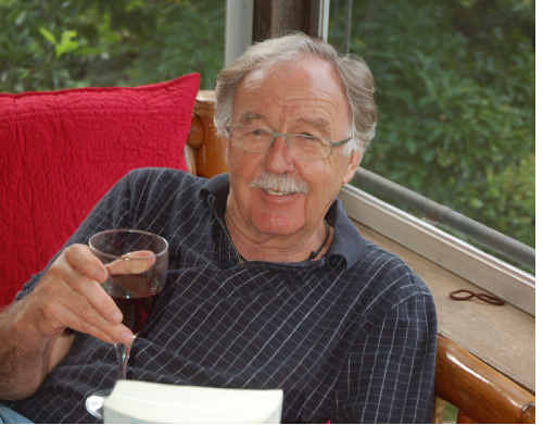 George Negus enjoys a glass of red and a good read at his Bellingen home.