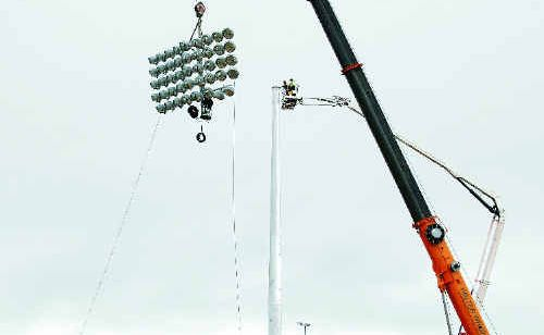 Richard Nimmett and Peter Burke prepare to attach the lights at the new Mackay Football Stadium.