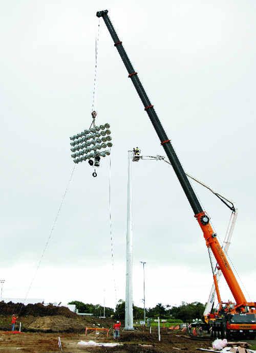 Richard Nimmett and Peter Burke prepare to attach the lights at the new Mackay Football Stadium.
