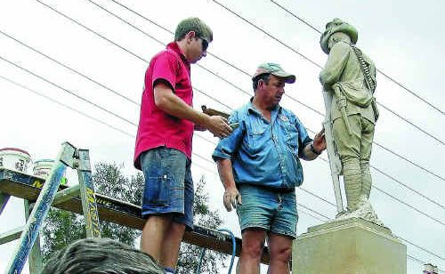 Allora RSL Sub Branch secretary Ken Ashton in front of the statue as Sam Holmes (left) and Robert Wagner fit the new rifle piece.