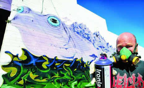 Ash Johnston working on a giant mural down the alley on Park Ave next to The Happy Frog.