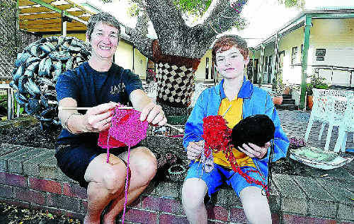 Annie Hackett, of Georgie's Cafe, and 10-year-old Samuel Page with some of the knit-wear for the Clarence Valley guerrilla knitting project. Photo: JOJO NEWBY