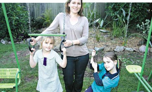Bella Gray, right, with mum Sarah and sister Olivia, have some fun at home.