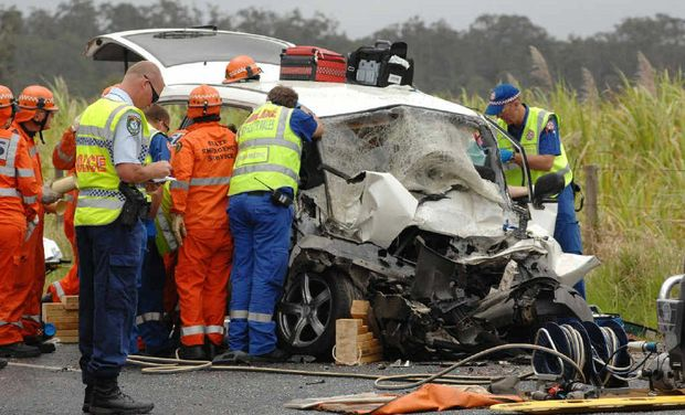 Rescue services try frantically to save the lives of two people trapped inside this vehicle involved in a double fatality on the Pacific Hwy at Chatsworth Island yesterday.