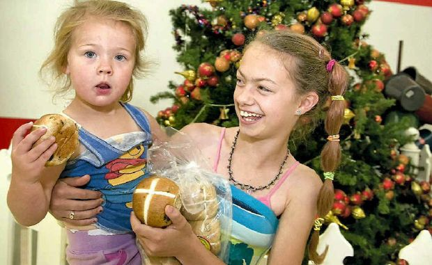 Sisters Eliza Parkes, 3, and Kimberley Anderson, 12, eat hot cross buns from Woolworths at the Wilsonton Shopping Centre more than three months out from Easter while Christmas decorations still adorn the halls.