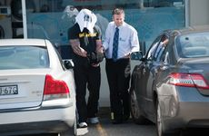 Police take the man into custody after his arrest on Thursday.