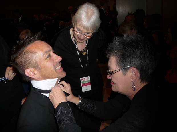 Heather Martin OAM makes a last minute fix to Sean O'Hara's bow-tie, while Doriel Worley supervises.