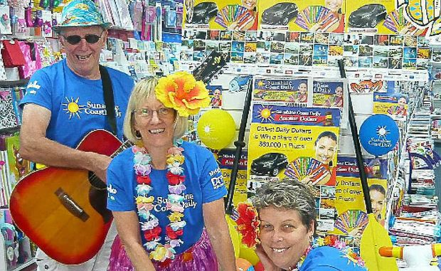 Local musician Kevin Brand gets into the spirit of the Daily Dollars promotion with Marlene Clews and Nicky Smith.