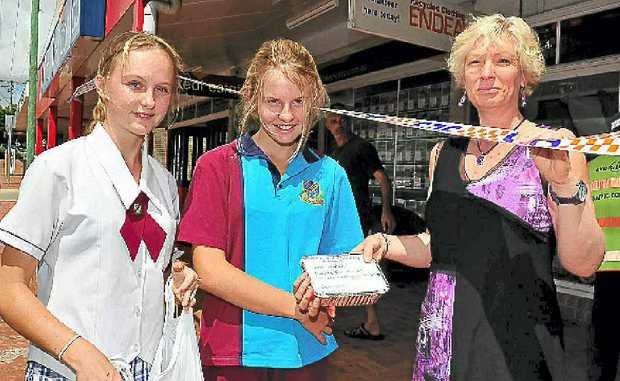 Noosa Christian College students Jessica Gray and Katie Waho give homemade muffins to Karen Tyack at Cooroy Shoes.