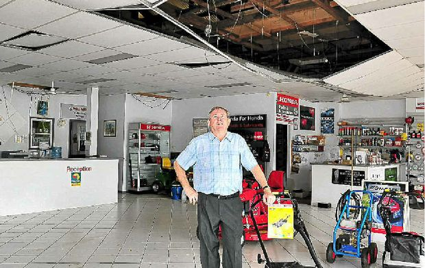 Daddows sales manager Neil Dwyer inspects the premises' damaged roof as the big clean-up continues in Cooroy.