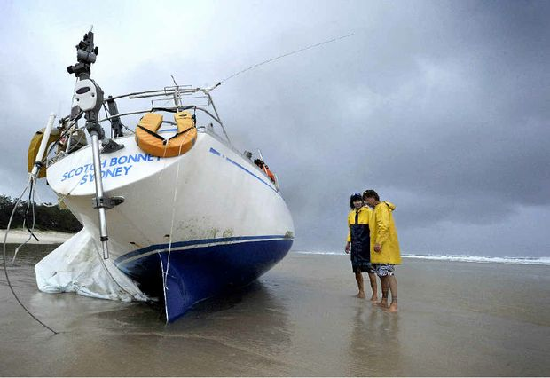 Brunswick Heads locals Ashley Virgo, left, and Colin James, survey the condition of the Scotch Bonnet washed up on Brunswick Heads Main Beach, believed to be an abandoned yacht from New Zealand. Photo Cathy Adams / The Northern Star
