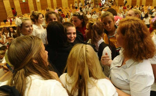 Ariel Morrissey is hugged and congratulated by friends after having her head shaved at the Shave for a Cure event at South Grafton High School yesterday