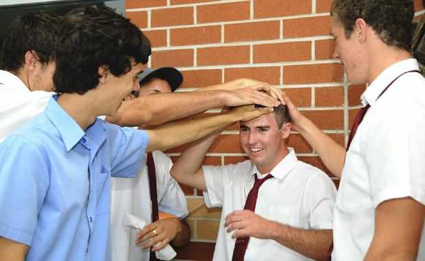 HEADS UP: Sam Hall is mobbed by his mates wanting a chance to feel his newly shaved head after he lost his locks for Shave for a Cure. The McAuley Catholic College Year 12 student had a very personal reason for doing the shave, after loosing his father Mark Hall to cancer. Photo: JoJo Newby