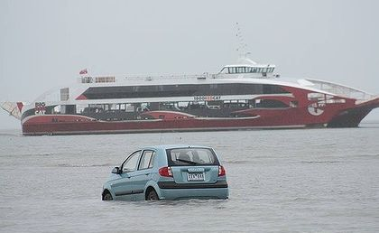 The Big Red Cat sails past the tourists' car. The low tide and a GPS navi