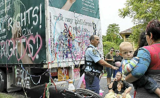 KEEP CALM: Police talk to protesters at Sunday's gathering against the anti same-sex truck.