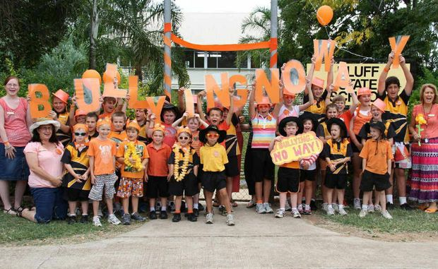 Students and staff at Bluff State School say no to bullying by designing signs and standing at the front gate in a sea of orange.