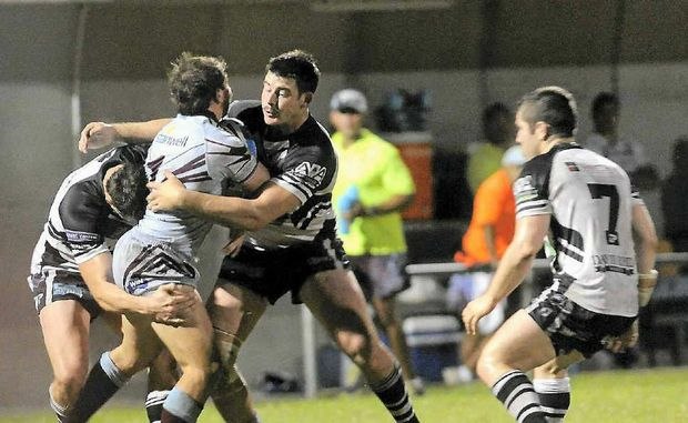 Magpies players swoop on Capras fullback Reece Baker during the Intrust Super Cup match at Marley Brown Oval.