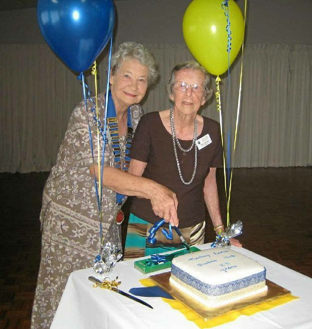 President Wilma Smith and Reta Taylor cut the 25th anniversary cake.