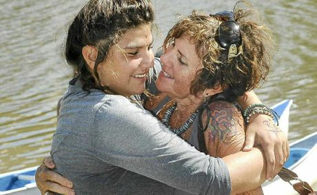 Keshaya Williams from Cabarita is greeted by her grandmother Mignon Francis at the end of the 10-day outdoor adventure and, at left, canoes under the Ballina Street bridge.