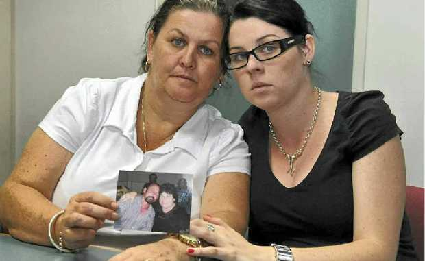 Julie Stevenson holds a photo of her husband Paul Stevenson and is comforted by daughter Nikki.