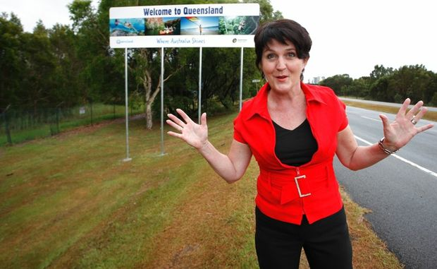 Minister for Tourism, Jann Stuckey poses for a portrait with a 'Welcome to Queensland' sign.