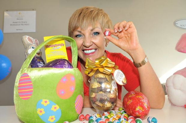 Annette Sym-Easter health story. Annette is displaying a variety of chocolate Easter eggs.