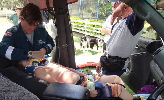 Paramedics attend to an eight-year-old boy who was sucked into a storm water drain west of Mackay.