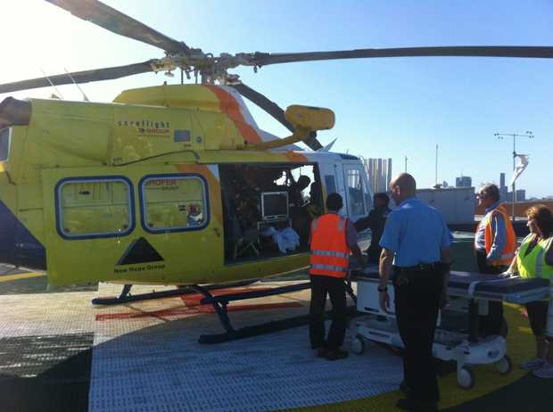 A woman was airlifted to Brisbane after she was crushed by her own car.
