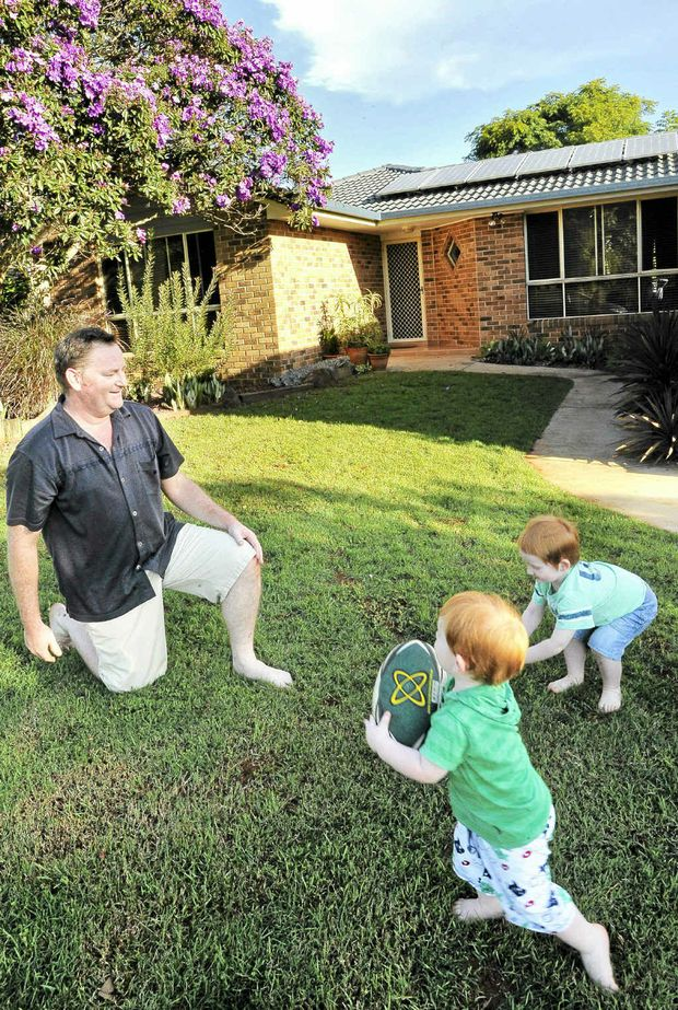 Richard Lutze spends time with sons Damien, 3, and Jeremy, 2, happy that his electricity bills are lowered by solar panels.