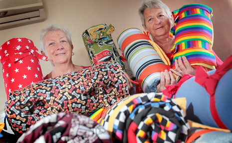 HELPING HANDS: Dianne Hanney and Pam Marshall have been making bags filled with quilts and toys for kids who will be going to camp quality.
