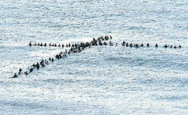 The Christian Surfers crew make a cross formation at sunrise off First Bay at Coolum.