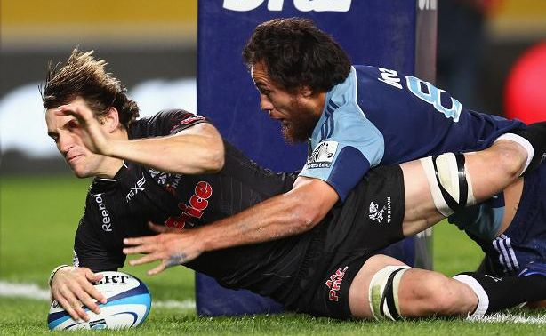 Keegan Daniel of the Sharks scores a try in the tackle of Chris Lowrey of the Blues during the round eight Super Rugby match between the Blues and the Sharks at Eden Park.