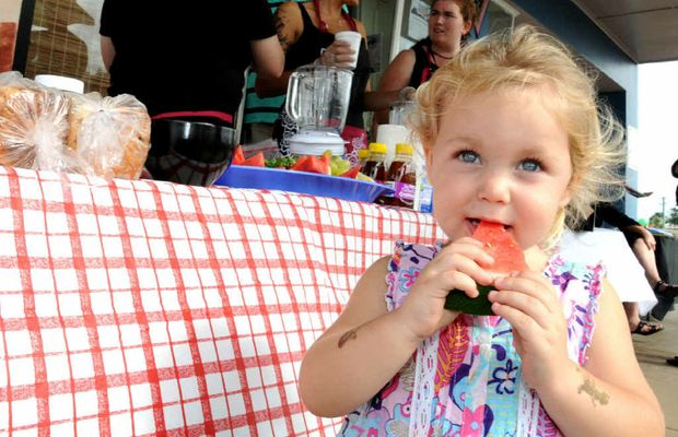 Helaina Taylor enjoys a piece of watermelon at yesterday's free healthy breakfast for National Youth Week.