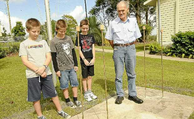 School captains Declan (left) and Sean Allen and Fletcher Creed with project manager Fred Hoskings at the new foundation for the Anzac memorial at Wyrallah public school.