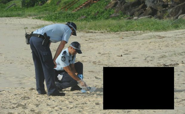 Police on the beach at Palm Beach with the man's body.